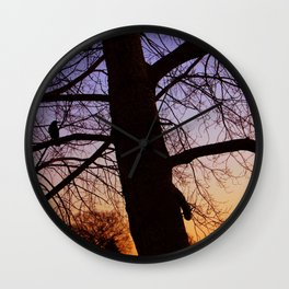 Bird watching the sunset Wall Clock