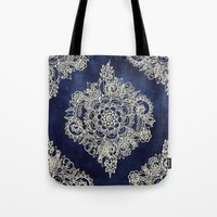 teagan white Tote Bags featuring Cream Floral Moroccan Pattern on Deep Indigo Ink by micklyn