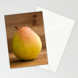 One fresh pear with water drops on rustic wood against a rustic wooden background close front view Stationery Cards