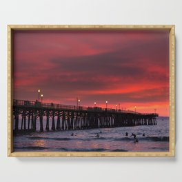 Surfers riding waves off Seal Beach pier at sunset Serving Tray