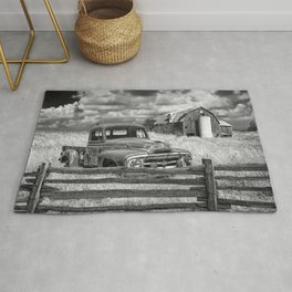 Black and White of Rusted International Harvester Pickup Truck behind wooden fence with Red Barn in Rug