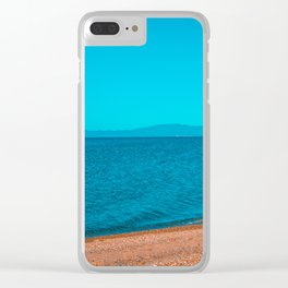 stony beach with mountains in the background Clear iPhone Case