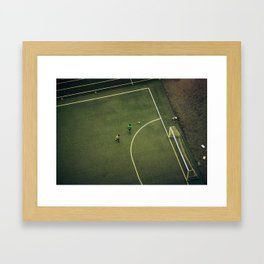 Kids are playing football on the green field Framed Art Print