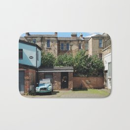 Vintage Blue Car in a Bright Glasgow Tenement Building Courtyard Bath Mat