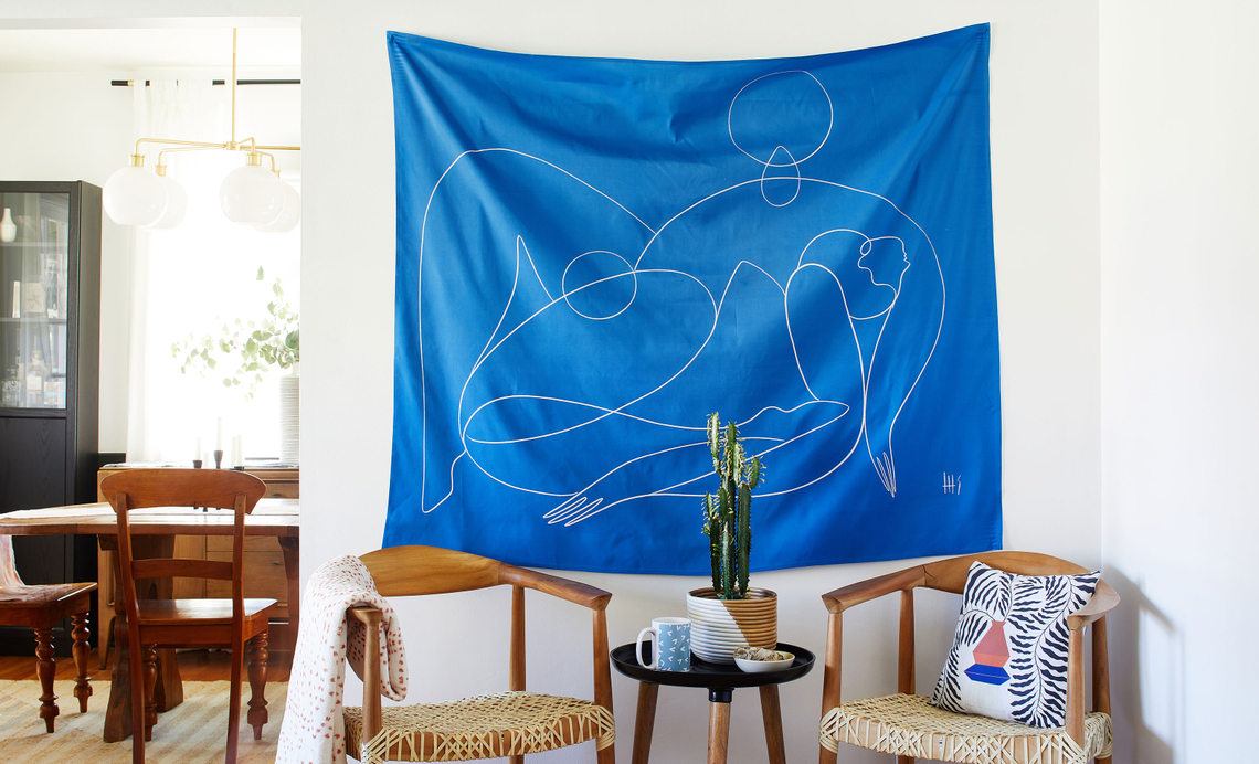 living room with blue minimal line drawing tapestry