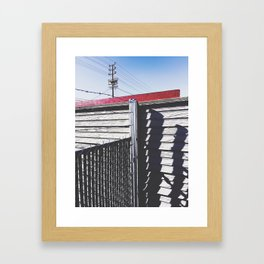 steel fence and wooden fence with red building in the city Framed Art Print
