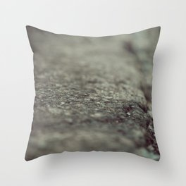 Blurry view to a damaged spot on the asphalt Throw Pillow