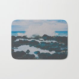 blue wave crashing on black rocks with tide pools Bath Mat
